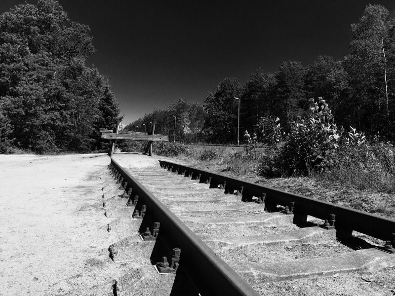 Black and white photo: train tracks at the end of the line